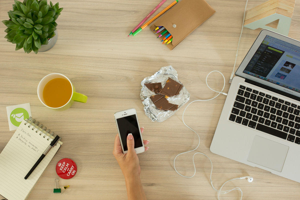 A woman is holding a phone while working on her notebook. Blogging can be time consuming for busy professionals. Here is a blogging guide to help.